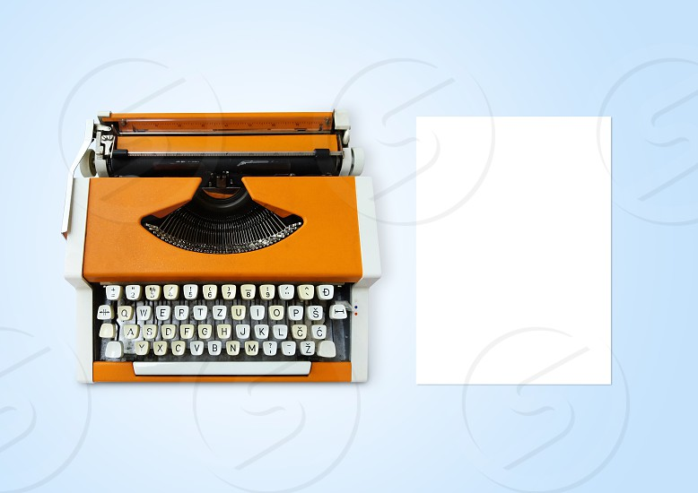 Typewriter and empty sheet of paper on light blue background table top view photo