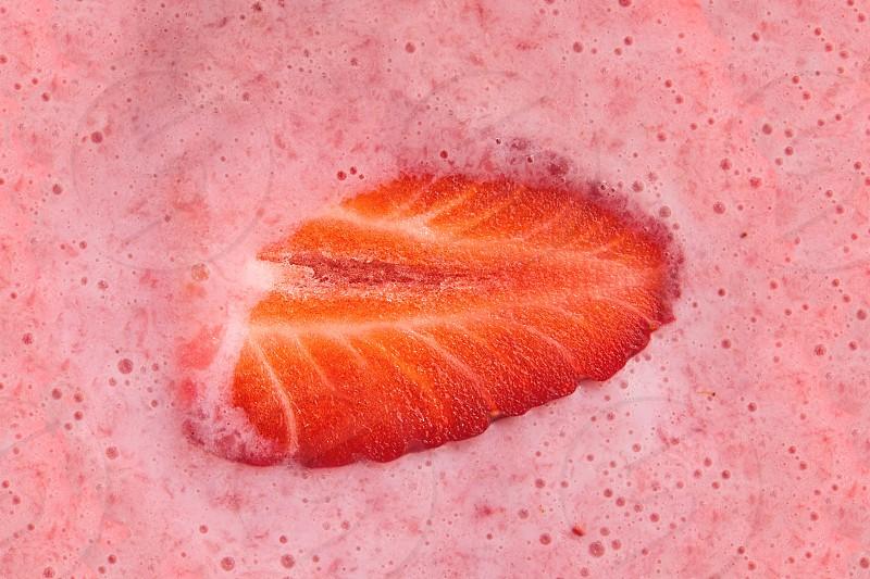 Halved Strawberry in Milk Shake Closeup Top View photo