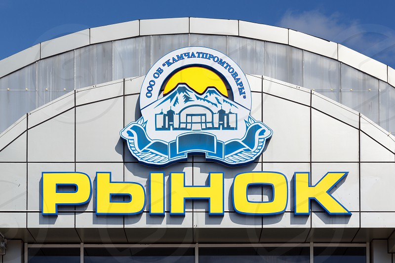 "PETROPAVLOVSK KAMCHATKA PENINSULA RUSSIA - AUG 29 2017: Signboard in russian: ""Market"" (""Kamchatpromtovary"") and company logo. This market - of busiest trade places in Petropavlovsk-Kamchatsky City photo"