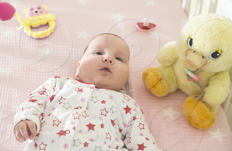 Baby girl in a bed with toys around. Pink tones photo