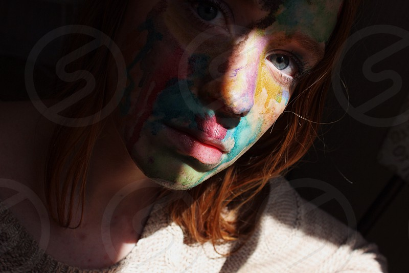 red haired woman wearing white knitted shirt with blue red and yellow face paint photo