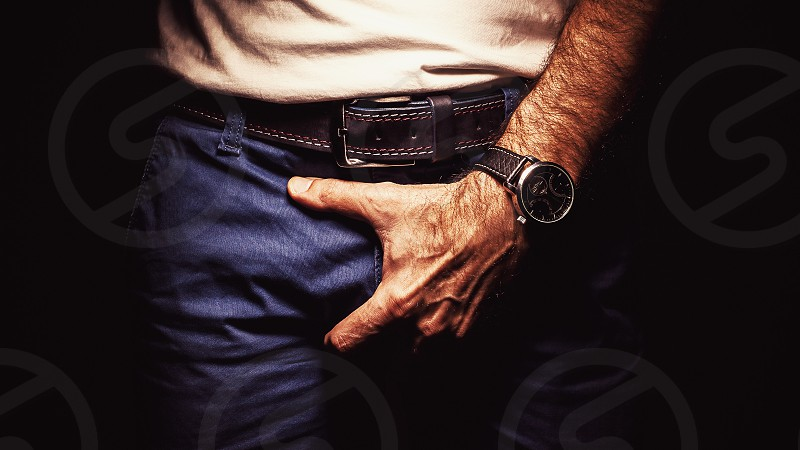 Male person is holding his pants.  photo