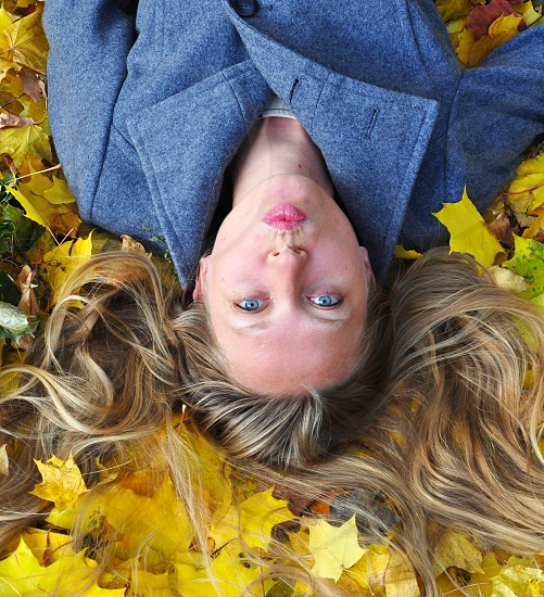 Blonde girl laying on the yellow leaves  photo