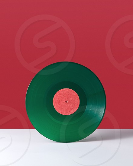 Green music record on a double white red background with space for text. Retro audio technology photo