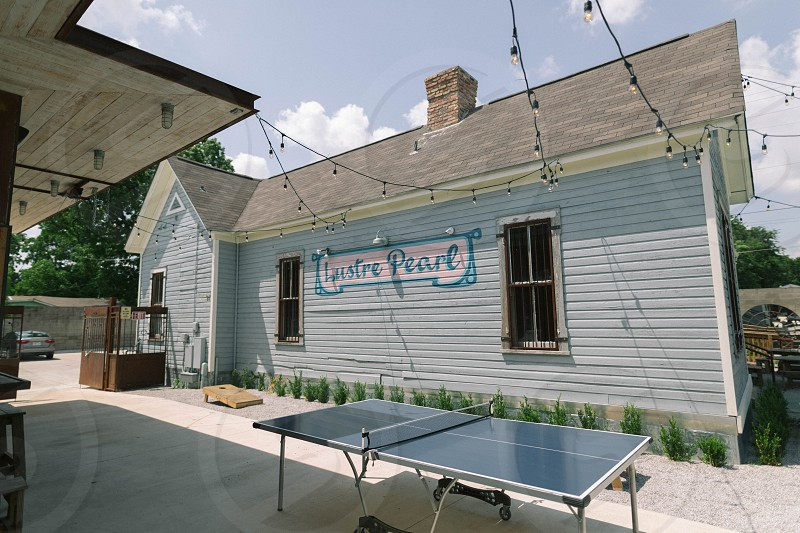 ping pong table near house with desire pearl signage during daytime photo