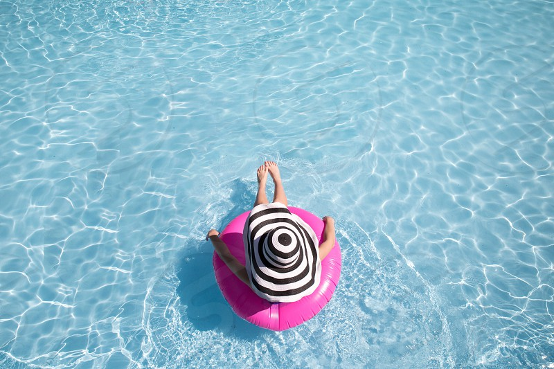 woman on pink inflatable lifesaver drifting in the pool photo