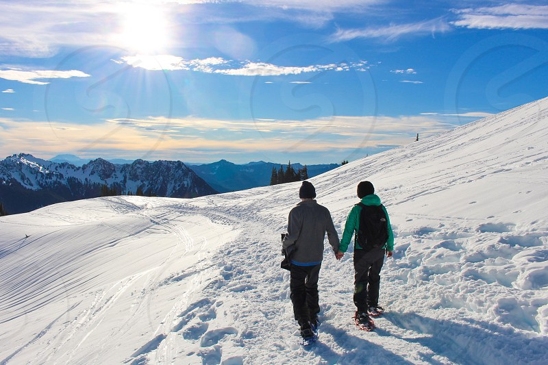 Snow winter couple holding hands hiking snowshoeing mountains white snowing sunny wilderness cold chilly weather seasons seasonal holidays  photo