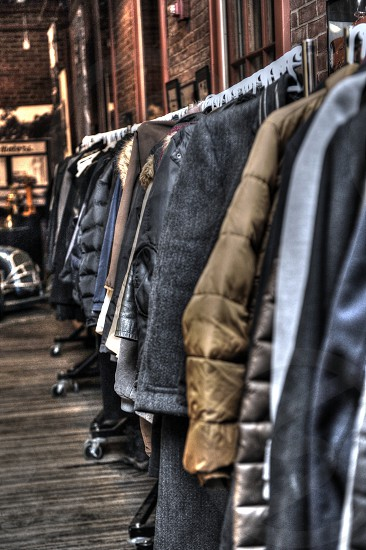 Winter coats hanging on a long coat rack inside a building with brick walls. photo