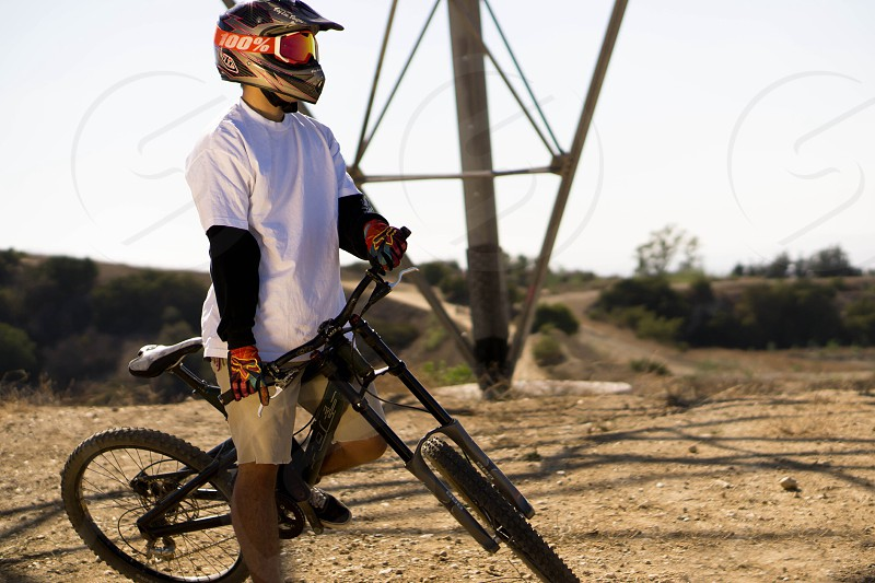 biker wearing white crew neck t shirt and red black helmet riding black hardtail mountain bike photo