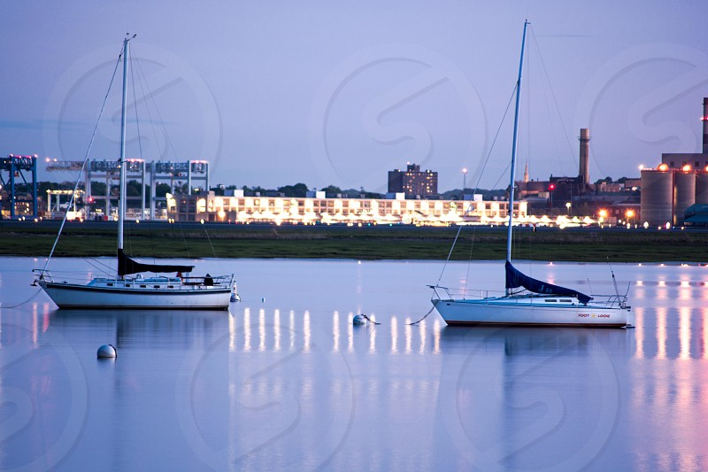 white sailing boat in body of water facing white sailing boat during nighttime photo