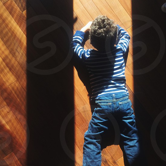 boy in blue denim jeans and blue and white striped long sleeve shirt lying on floor photo