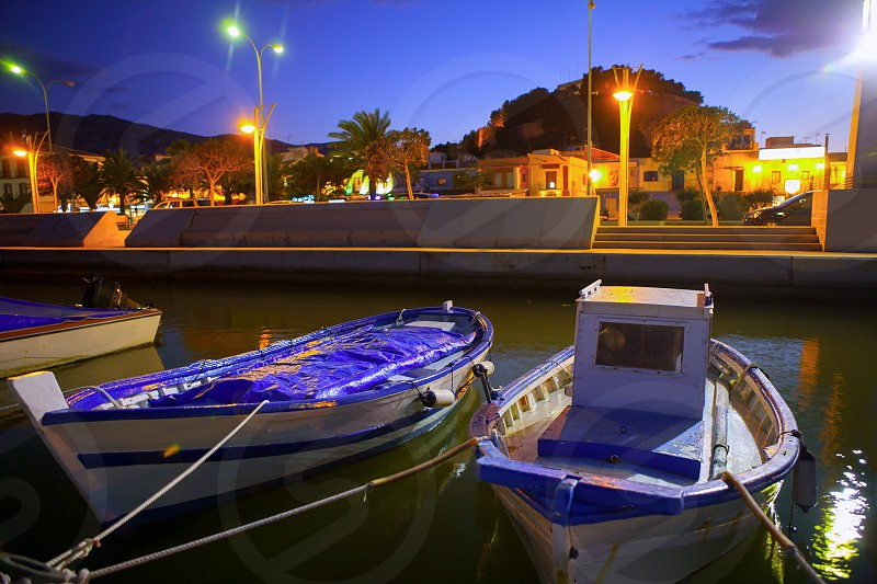 Denia port marina with traditional llaut boats at sunset night Alicante Spain photo
