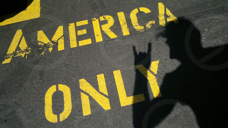 america only yellow text on gray pavement photo