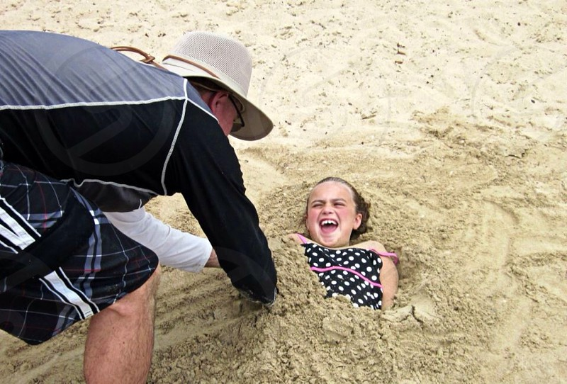 man in black and grey shirt burying girl in beach sand photo
