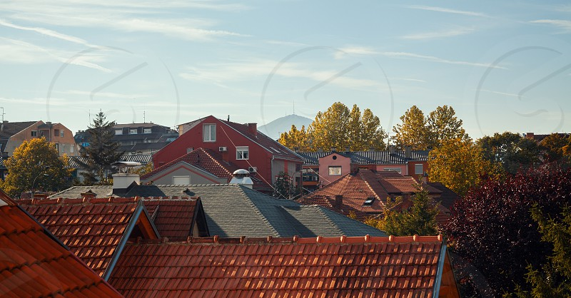 Autumn landscape of a small Balkan town just colorful trees and roofs. photo
