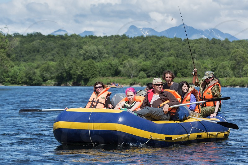 BYSTRAYA RIVER KAMCHATKA PENINSULA RUSSIAN FAR EAST - JULY 13 2016: Summer rafting on Kamchatka - group of tourists and travelers floating on calm river on raft on background of green forest and mountains. photo