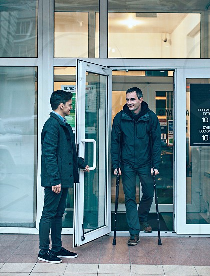man in black jacket walking with medical crutches beside man during daytime photo