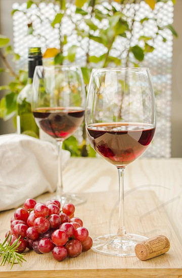 Two glasses of red wine and grapes photo