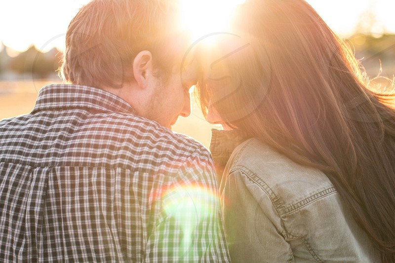 couple with their heads together with the sunset shining through photo