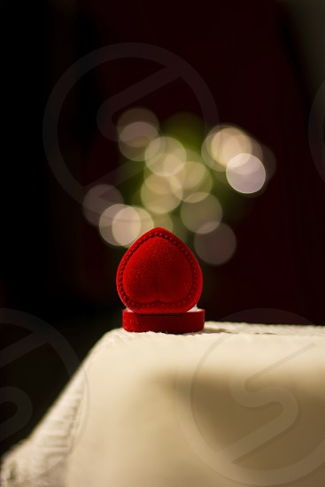 Small red gift box in shape of heart opened and lights above photo
