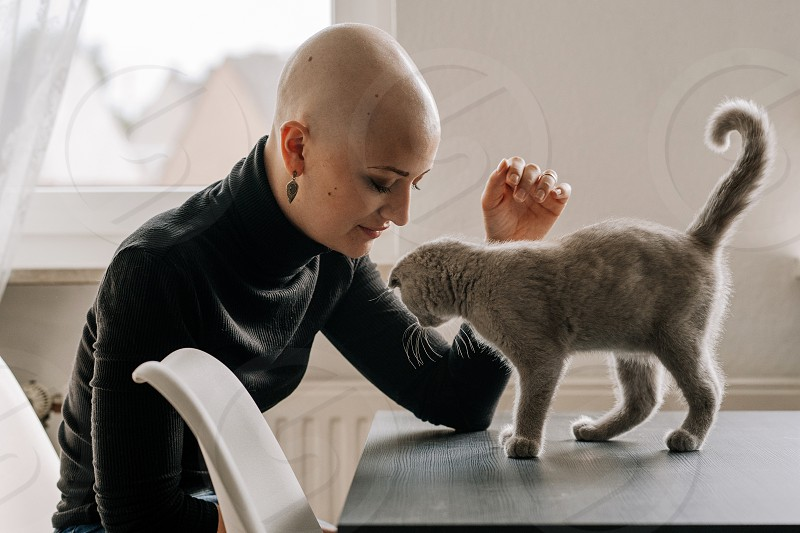 strong woman fighting breast cancer plays with cat at home photo