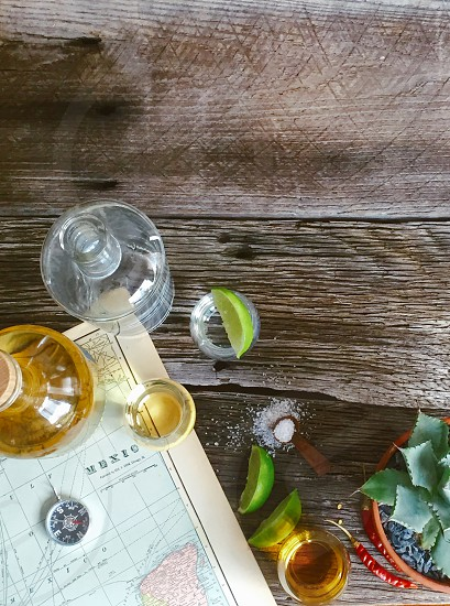 top view of tequila bottle and lemon near beside the map on brown wooden plank photo