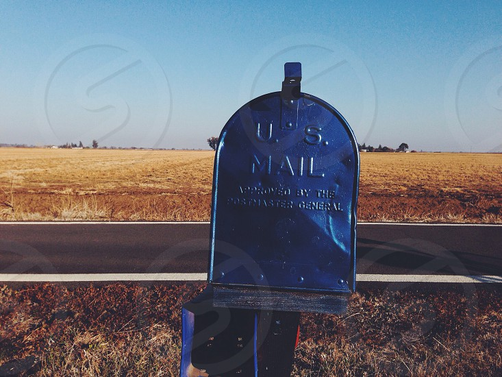 blue steel u.s mail box on brown field photo