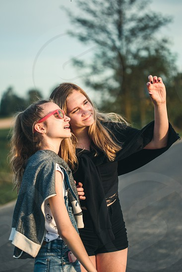 Teenage smiling happy girls having fun walking outdoors hanging spending time together on summer day photo