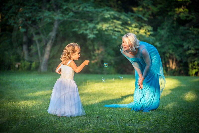 Grandmother blowing bubbles with her grand daughter. photo