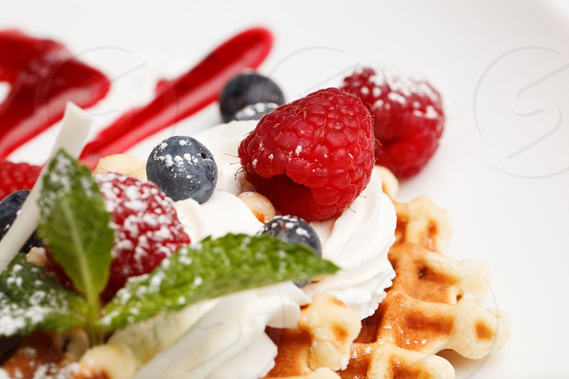 Waffle and cream topped with fresh blueberries and raspberries and garnished with peppermint focus to a ripe raspberry photo