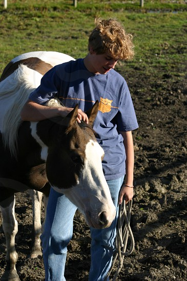 man in blue yellow crew neck t shirt beside white and black horse in field photo
