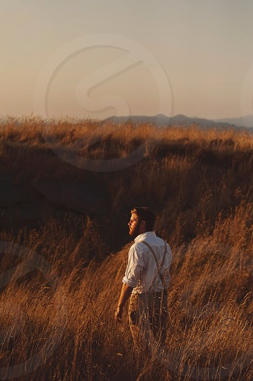 profile of a man with a beard wearing a white shirt with suspenders standing in tall brown grass reeds with hill in the distance looking towards the sunset photo