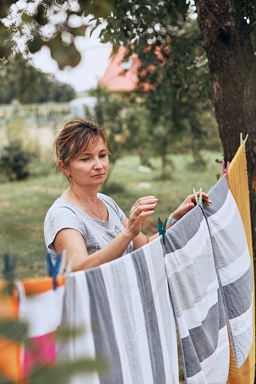Mature woman hanging a freshly laundered bed linen on clothesline stretched between two trees in a orchard. Candid people real moments authentic situations photo