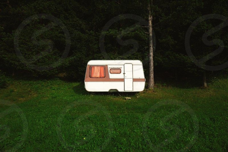 Old camper on filed besides the dark wood.  photo