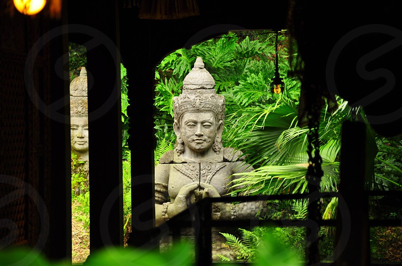 2 gray thai god statues near green ground cover plants during daytime photo