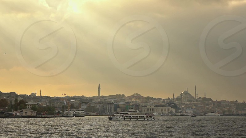 Panoramic view from the ship in Bosphorus strait to cityscape with Suleymaniye mosque in a sunbeams and travel ships at sunset background. Slow motion Full HD video 240fps 1080p. photo