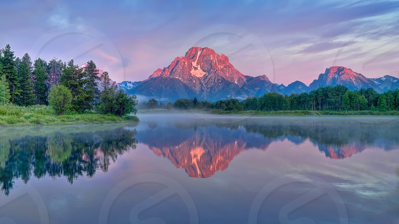 """""""Oxbow Glow"""" Sunrise kisses the Grand Teton Mountain Range exploding with color and radiance and is reflected at Oxbow in the Snake River at Oxbow Bend. photo"""