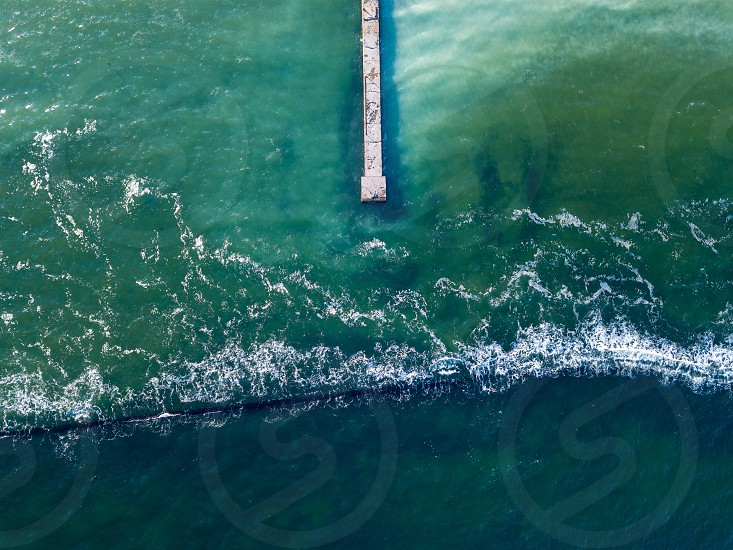 Top aerial view from drone to seascape with clear turquoise water breakwater and pier. Natural marine background with foam waves. Place for text. photo