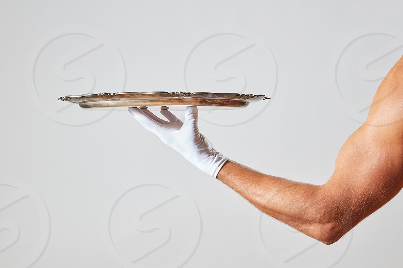 Muscular hand of waiter in a white glove holding a silver vintage empty tray on a white background with place for text. photo
