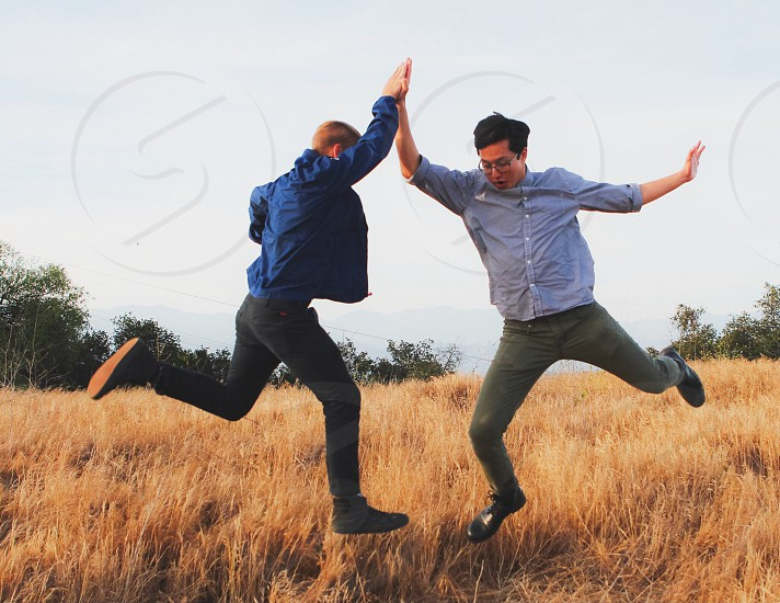 two men in blue button down shirts high fiving in a tall brown grass field photo