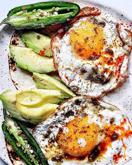 Breakfast tortillas with zaatar fried eggs jalapenos and avocado photo