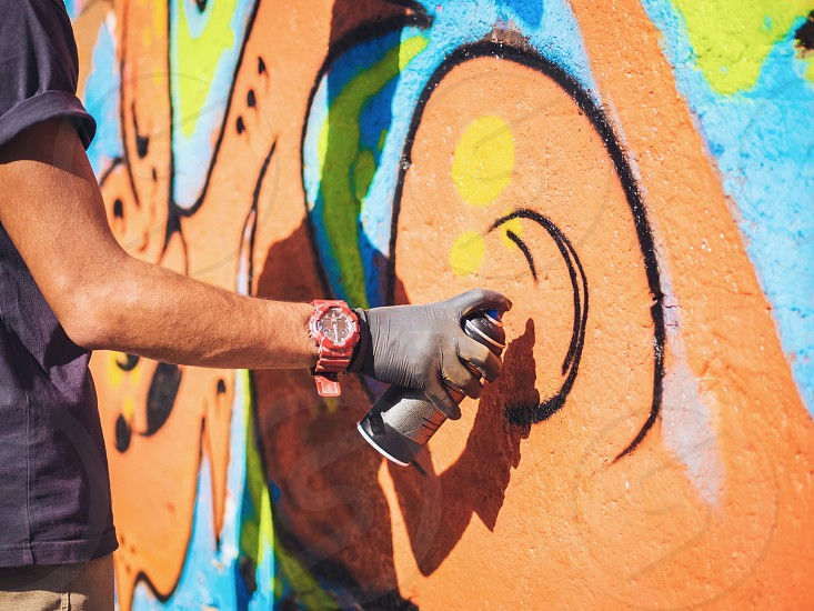 Graffiti Artist Painting On The Street Wall. Male hand with aerosol spray bottle spraying with colorful paint Urban Outdoors Art Concept. photo