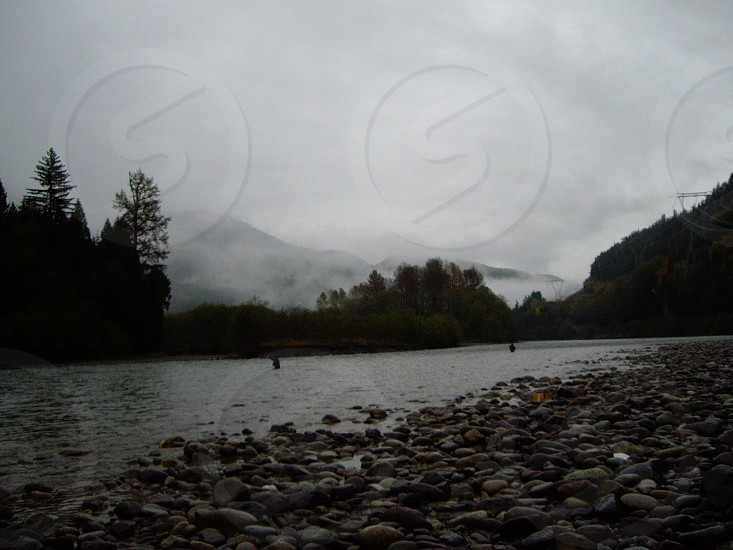 Fog lifting from river with anglers astream photo