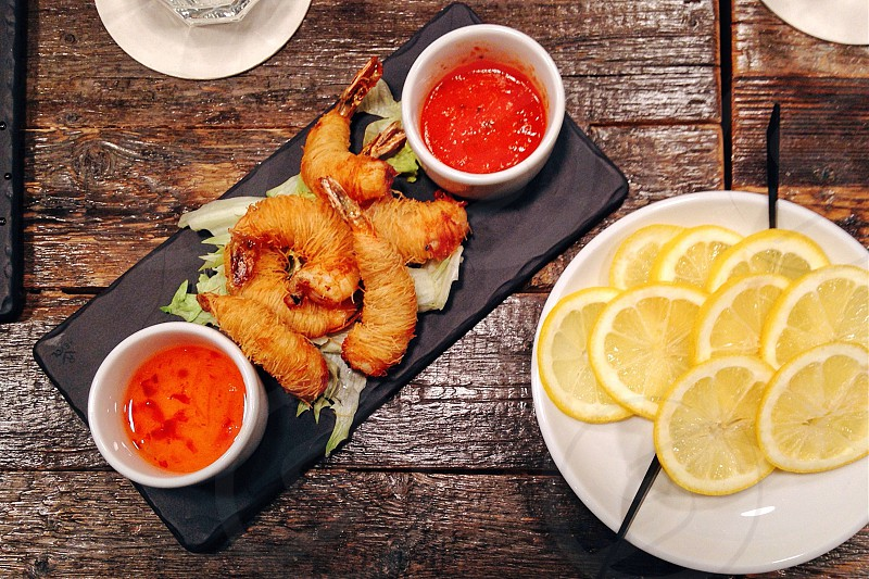 Prawns with sauce and lemon wedges photo