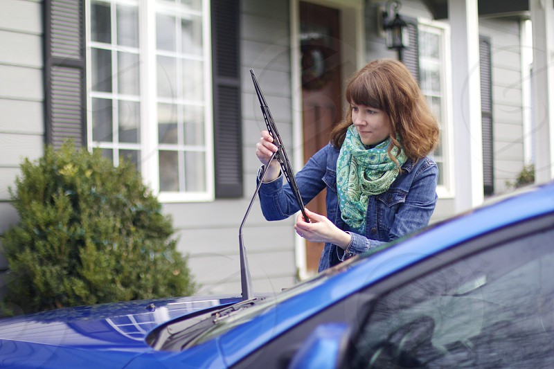 woman wearing blue denim jacket fixing black car windshield wiper photo