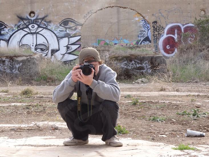 man wearing gray hoodie holding black camera  photo