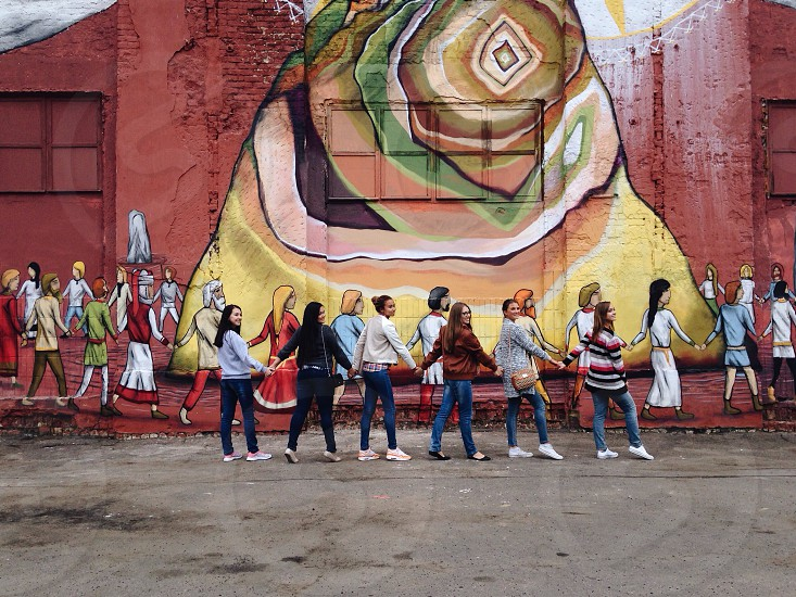 group of 6 women holding their hands in front of concrete wall with group of people holding their hands mural during daytime photo