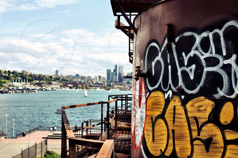 grafitti on side of tower overlooking water photo