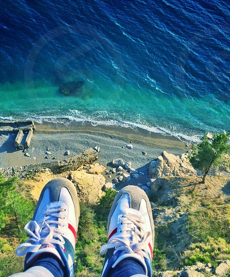 person sitting on top of mountain and top view of seashore photo