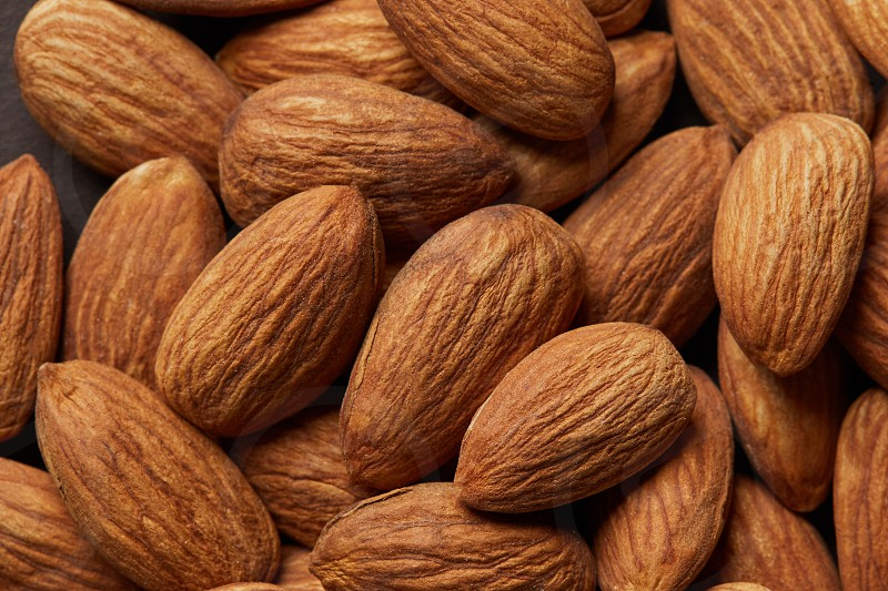 Close up of a pile of almond background top view. Food healthy concept for vegetarians photo